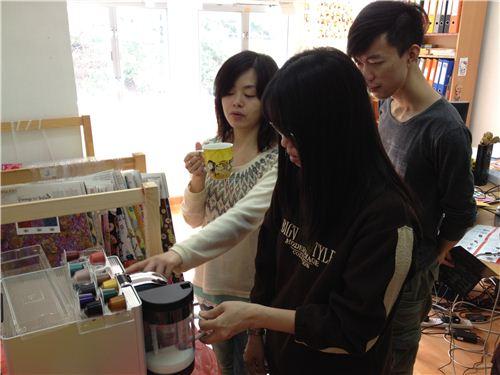 Karen shows Sylvania how to use the Nespresso machine