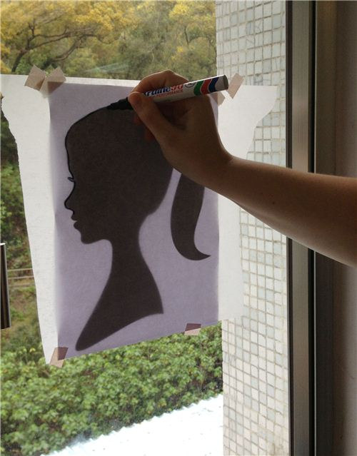 Sketch the outline of the head with a marker on the baking paper by sticking it onto the picture on a window